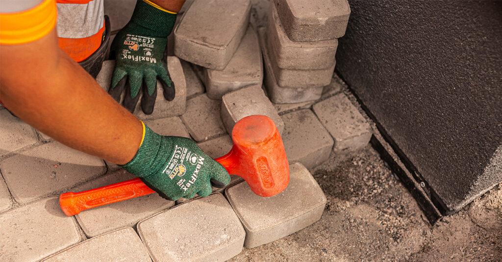 Piha Siistiksi kivimies asentamassa pihakivetystä. Lähikuvassa kädet, kiviä ja nuija.