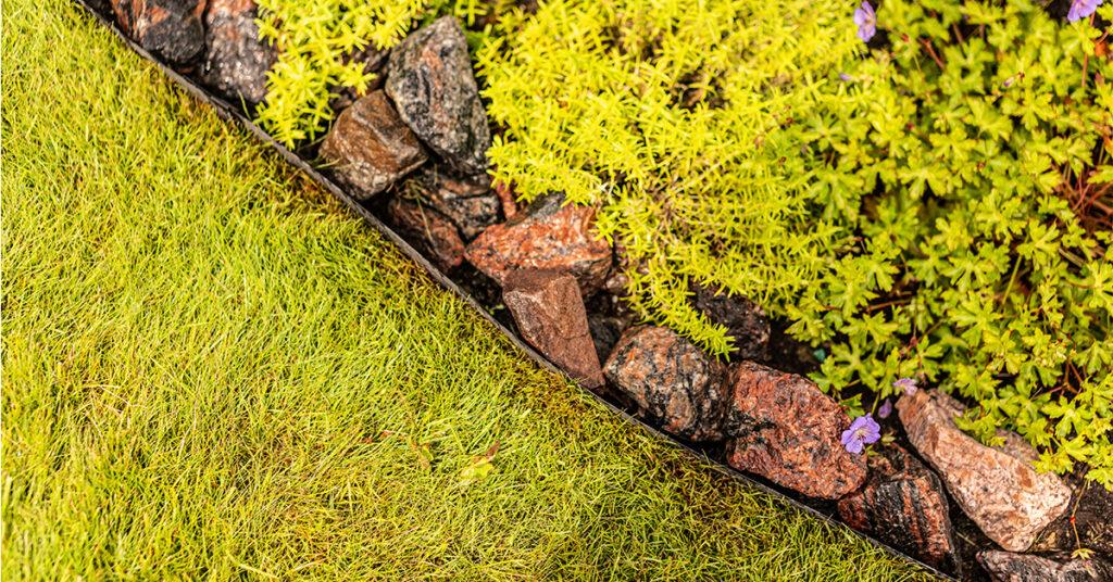 Siirtonurmen ja kivi-istutuksen väliin asennettu puutarhareunus